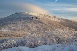Hoarfrost on the tree against Ipseokdae Rock of Mudeungsan Mountain with cloud at Dong-gu near Gwangju, South Korea