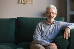 Hoary senior man in casual clothes sitting aside on couch in living room pose look at camera copy space for text, elderly single grandfather in glasses alone at home, healthy satisfied retiree concept