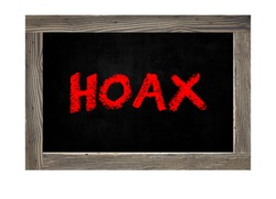 Hoax conept word on a chalkboard background. Chalkboard with danger sign with words Internet Hoax, Danger of Internet Hoax.