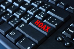 Hoax word on red keyboard button. Computer keyboard key with danger sign with words Internet Hoax, Danger of Internet Hoax.