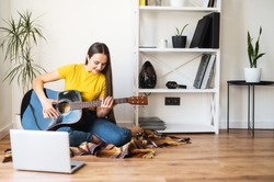 Hobbies and leisure activities during quarantine. Online training, online classes. A young woman watches a video lesson on playing the guitar, she sits on a cozy plaid with a guitar