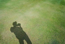 hobby and lifestyle activity from shadow of photographer man on green grass during hold his camera  and take picture