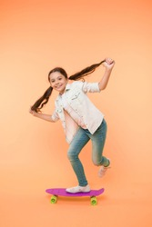 Hobby favorite activity. Child smiling face stand on skateboard. Penny board cute colorful skateboard for girls. Lets ride. Girl ride penny board yellow background. Kid having fun with penny board