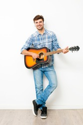 hobby for boys. man playing the guitar with headsets on his head, enjoying his spare time in his own house, doing what he likes, on white background, full lenght
