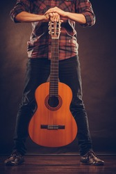 Hobby, music concept. Person is standing with guitar. Man is holding the instrument.
