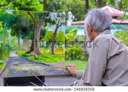 HOCHIMINH CITY, VIETNAM - JULY 19: unidentified artist is painting a picture at Botanic garden in Hochiminh city, Vietnam on July 19, 2013.Hochiminh city is biggest city in South Vietnam.