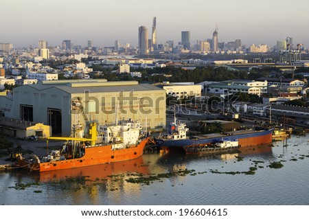 HOCHIMINH CITY, VIETNAM - MAY 31:Ship repair plant on Saigon river and city center on riverbank in Hochiminh city, Vietnam on May 31, 2014.