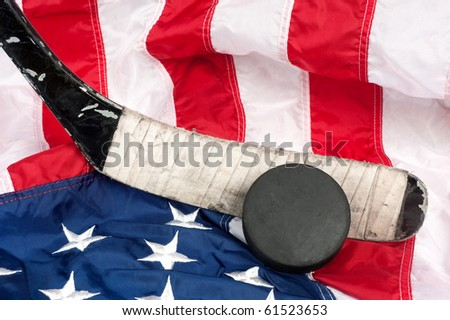 Hockey equipment including a stick and puck on an American flag to infer a patriotic American sport. - stock photo