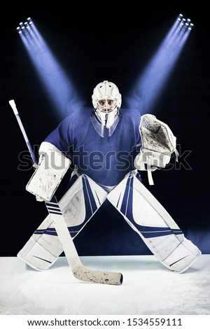 Hockey goalie stands in the spotlight ready to catch the puck.Hockey goalie in complete hockey gear  standing in front of black background. Above him are blue spotlight.