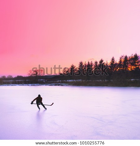 Hockey player silhouette on ice. Sunset sky in background. #1010255776
