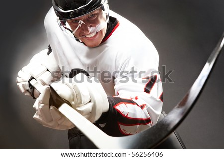 Hockey player with cruel facial expression pointing stick into camera