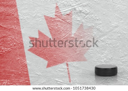 Hockey puck and Canadian flag on ice. Concept, hockey