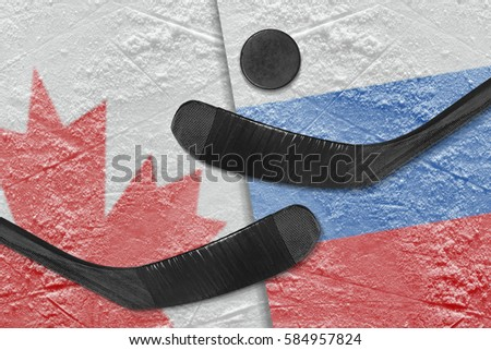 Hockey puck, hockey sticks and a picture of the Canadian and the Russian flag on the ice. Concept