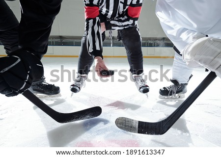 Hockey referee with puck standing on ice rink with two rivals with sticks on his right and left waiting for moment to shoot it