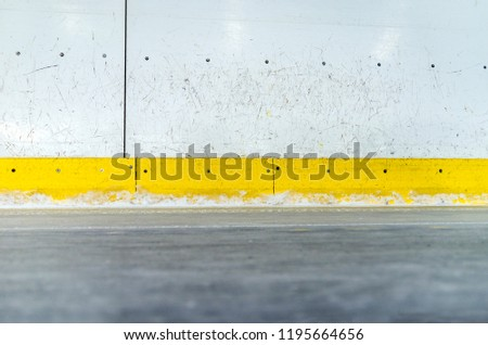 Hockey rink boards with scratched and damaged surface and ice floor #1195664656