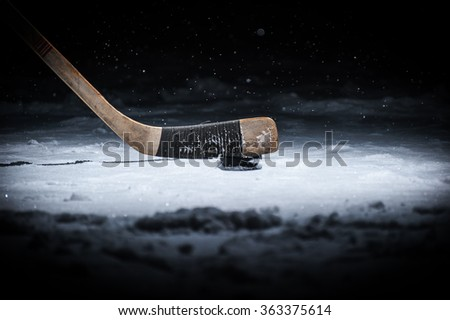 Hockey Stick and Puck on the Ice Rink