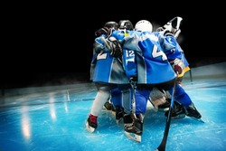 Hockey team standing in circle on ice rink