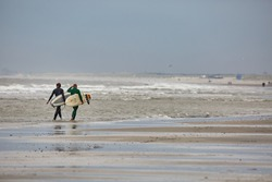 HOEK VAN HOLLAND, THE NETHERLANDS - CIRCA 2019: Surfers going in the North Sea at the sandy beach of the Hook of Holland strand, popular recreational area at the North Sea
