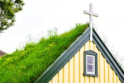 Hof, Iceland church closeup that was the last build in traditional turf style, Hofskirkja, building roof covered in green grass and cloudy sky background