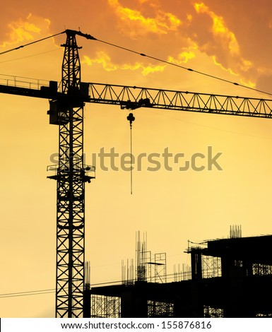 Hoisting crane silhouettes at sunset