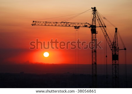 Hoisting cranes and construction site on sunset.