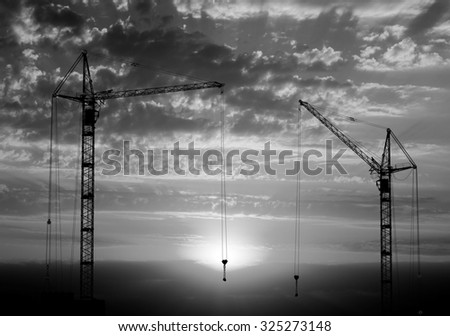 Hoisting cranes working on beautiful cloudy sky with sunset and rays of light background black and white