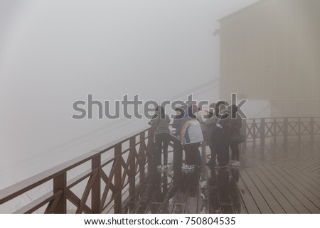 HOKKAIDO, JAPAN. APRIL 3, 2016: Tourists stand in the fog at observation area on the top of Mount Usu in winter in Hokkaido, Japan. #750804535