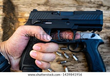 Hold a gun,Man holding a gun,Short gun,Noisy killing weapon,Deadly weapon #1439841956
