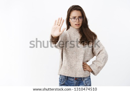 Hold, stop right here. Portrait of worried and displeased young female friend preventing girl sit in car drunk pulling palm towards camera in no prohibition gesture, worrying for safety over gray wall