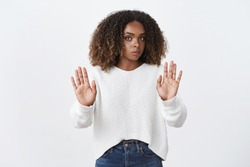 Hold your horses, slow down. Intense displeased and reluctant serious-looking african american female hearing disturbing proposal frowning and showing stop gesture, refusing and showing rejection