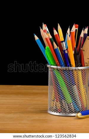 holder basket and school supplies isolated on black background