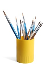 Holder with different paint brushes on white background
