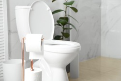Holder with paper rolls near toilet bowl in bathroom