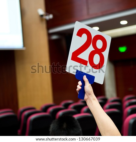 Holding a auction paddle - stock photo