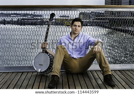 Holding a banjo a young musician is sitting on the deck, sincerely looking at you and thinking/Portrait of Young Musician