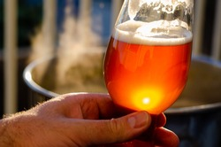Holding a beer in front of boiling wort for a home brewed beer as the sun sets and reflects off of the glass