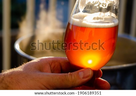 Holding a beer in front of boiling wort for a home brewed beer as the sun sets and reflects off of the glass Photo stock ©