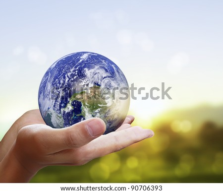 holding a glowing earth globe in his han - stock photo