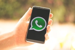 Holding a phone in hand with the WhatsApp app logo shown on screen