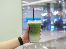Holding a plastic glass of iced green tea latte with layer of fresh foam milk blurred background, selective focus.
