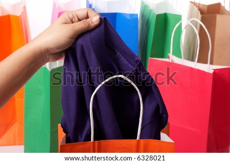 holding a shirt with some shopping bags on the background