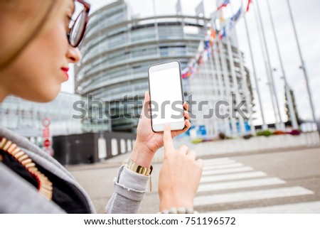 Holding a smartphone with empty screen to copy paste on the European parliament building background in Strasbourg, France