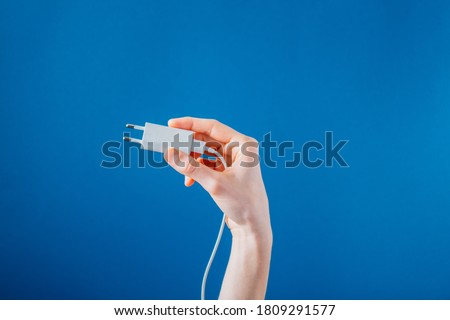 Holding A White Phone Charger On Blue Photo  A hand holds up a white European phone charger, the cord dangling off down the arm and the background blue as the skies. Stockfoto ©