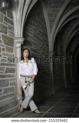 Holding a white rose and leaning on a wall, a young woman is lost in thought./I Miss You - stock photo