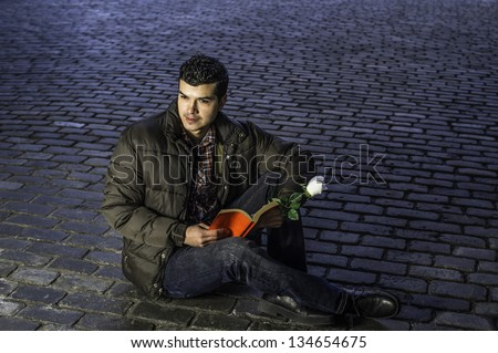 Holding a white rose and red book a young guy is reading outside/Wishing for love