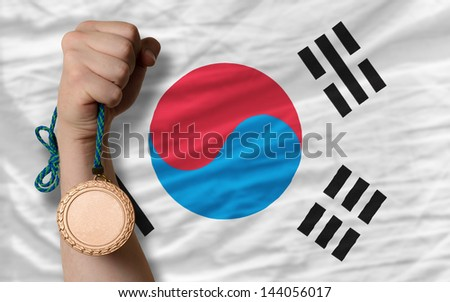 Holding bronze medal for sport and national flag of south korea