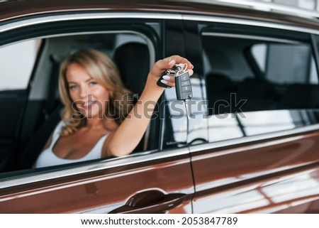 Holding car keys. Woman in formal clothes is indoors in the autosalon.