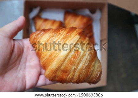 holding croissant, French bread or French croissant