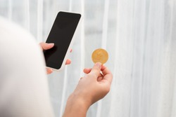 Holding crypto coin and mobile phone on white background