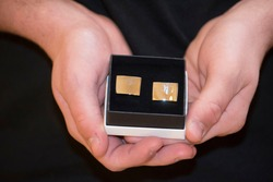 holding cufflinks for a suit, textile design and fashion trends